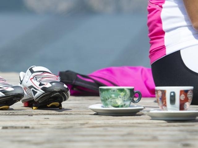 Eine sitzende Frau mit Sportsachen, zwei Kaffeetassen und Sportschuhen