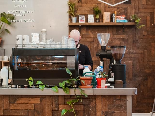 Ein Mann hinter einem großen Kaffeevollautomaten im Café
