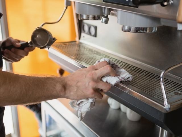 Eine Person reinigt einen Kaffeevollautomaten