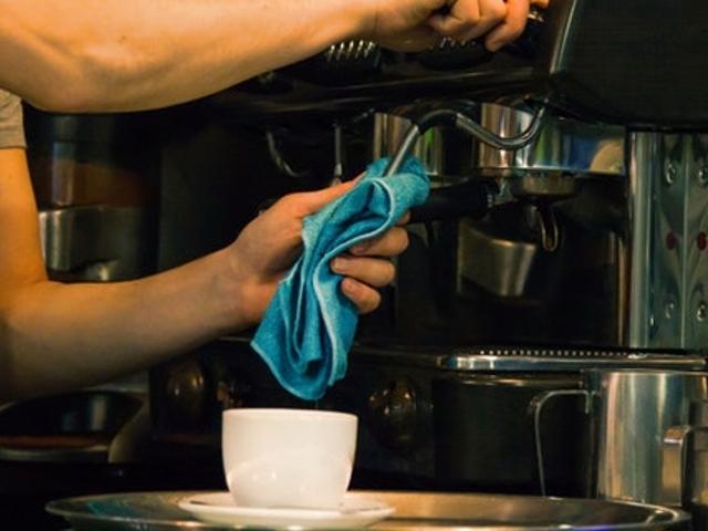 Eine Person säubert einen Kaffeevollautomaten
