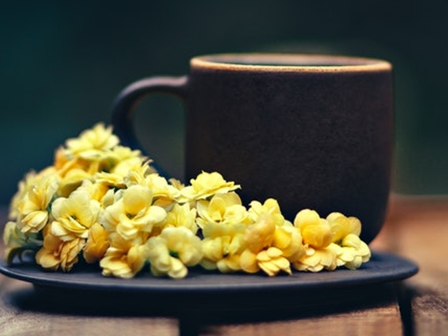 Eine Tasse Kaffee auf einem Unterteller mit gelben Blumen