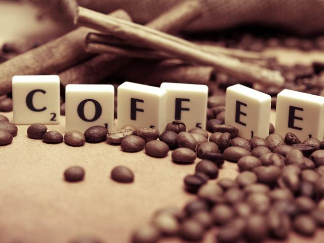 Das Wort Coffee steht auf Scrabble-Steinen geschrieben. Darum herum sind Kaffeebohnen gestreut.