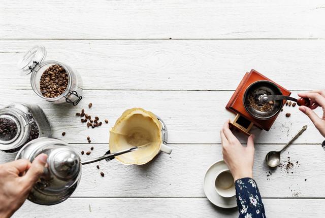 Mehrere Händen umfassen über einem Tisch eine Kaffeekanne und eine Kaffeemühle. Drumherum stehen Kaffeeutensilien wie Tassen und Bohnen.