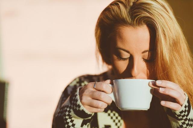 Eine blonde Frau trinkt genüsslich ihren Kaffee aus einer Kaffeetasse.