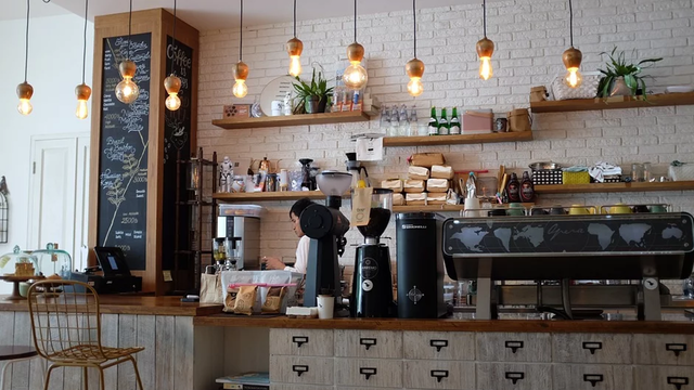 Eine Kaffeebar mit hölzerner Theke, einem Kaffeevollautomaten und einem beschäftigten Barista dahinter. Das Café wirkt hell und freundlich, Lampen hängen von der Decke und es gibt eine große Auswahl an Speisen und Getränken.