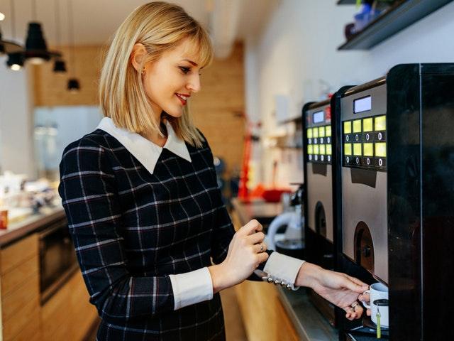 Eine junge Frau in Bürokleidung holt sich einen Kaffee am Vollautomaten
