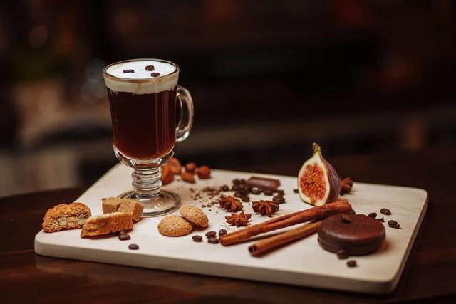 Eine gedeckte Tafel mit einem frisch zubereitetem Kaffee im Glas und anderen Leckereien drapiert.