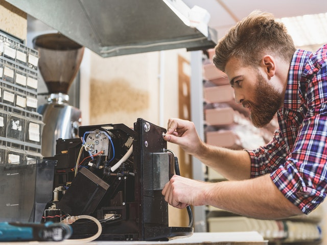 Ein junger Mann repariert einen Kaffeevollautomaten