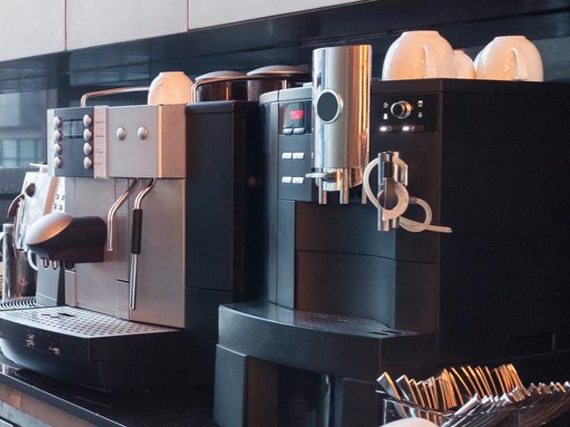 Zwei verschiedene Modelle von Kaffeevollautomaten mit Kaffeetassen und Milchaufschäumern