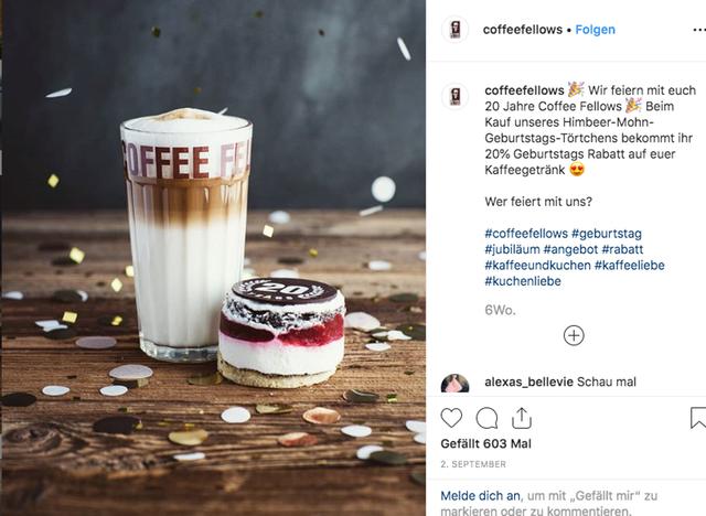 Ein Screenshot der Coffee Fellows auf Instagram. Zum Jubiläum weht Konfetti durch das Bild. Auf einem Holztisch stehen ein Latte Macchiato und ein pink-weiß-braunes Jubiläumstörtchen.